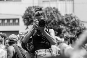 black and white crowd man rangefinder focus parade portrait woman taking photo outdoors