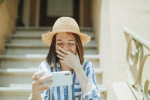 cellphone freckled sun hat steps smartphone laughing using enjoyment sitting cheerful