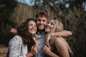 facial expression blond smile hugging man brunette friendship adorable depth of field female