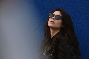 female outfit sunglasses fashion leaning wall brunette standing black leather jacket style