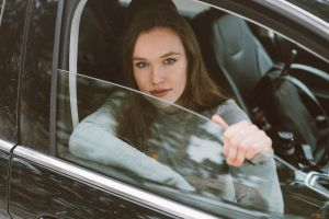 female person automobile transportation system daylight transportation vehicle portrait vehicle window looking