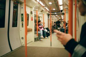 metro homeless orange focus phone train underground tube public people