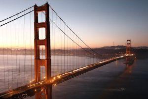 sunrise backlit city transportation system bridge landmark sunset sky clouds bay