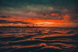 sunset beach cloudy sky water