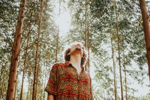 tall looking up fashion male sun glare outfit trees environment sunlight wear