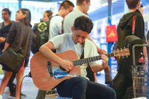 asian teen young teenager harbour guitar street musician male live performance music