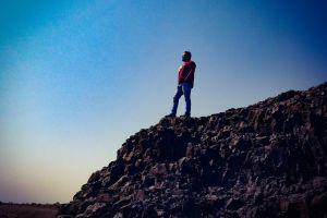 climber rocks man rock climbing sky person adult hike landscape adventure