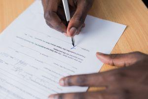 desk paperwork close-up office person writing signature ballpen pen handwriting