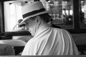 facial expression gentleman man people adult black and white wear restaurant indoors hat