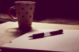 folder pen wooden desk wood colors close-up cup blur indoors