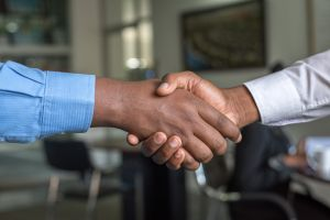 hand shake indoors blurred background chairs office formal people deal wear office people