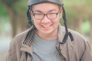 helmet daylight close-up smiling man blurred background jacket young facial expression eyeglasses