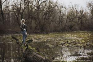 landscape pose woman daylight log weather marsh trees water reflection