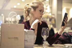 looking phone glamour elegant woman beautiful pretty focus paper bags smartphone