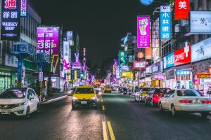 people buildings shops vehicles stores traffic road night time street urban