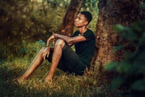 sitting male person boy young man solitude trees grass park