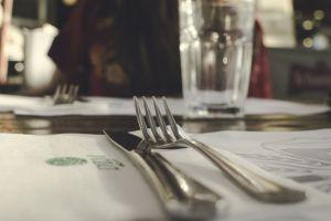 tablecloth tableware indoors forks flatware furniture close-up room blur knives