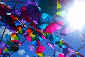 vibrant spectrum colours sun umbrella blue sky low angle photography rainbow sky low angle shot