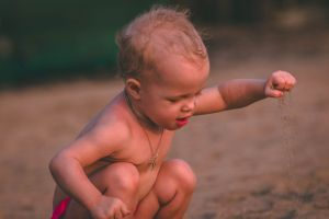 baby necklace kid facial expression sand child boy son person little