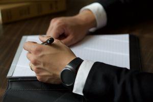 corporate office notepad man desk pen indoors corporate attire businessman person