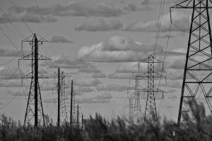 danger grid power lines grass low angle shot clouds black and-white transmission energy line