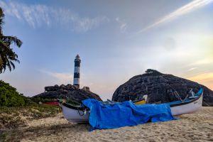 daytime scenic sand tree lighthouse sky landscape shore rocks seashore