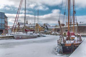 dock buildings watercrafts winter harbor port boats docked daylight pier