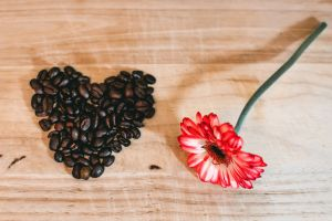 flatlay heart flower flora coffee beans pink flower close-up roasted coffee beans from above wooden