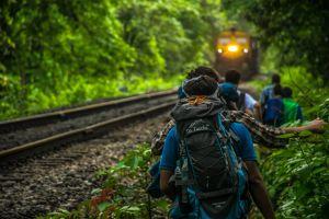 grass wear landscape backpack railroad track people train locomotive train tracks motion