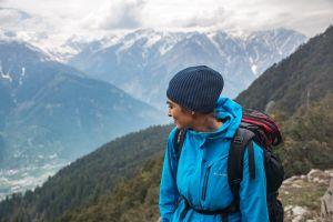 hike adventure mountain peak woman person mountains rocks snow jacket clouds