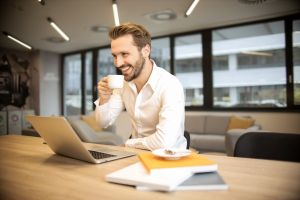 indoors workspace telephone laugh coffee laptop room workplace facial hair smiling
