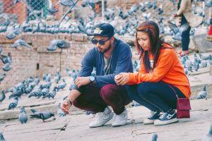 man sunglasses young couple brickwall woman young birdwatching cap urban people