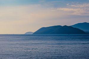 mountain horizon sky water beach daylight seascape landscape ocean dawn
