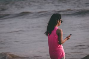 ocean mobile seashore beach waves girl sea daytime cellphone water