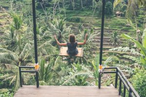 woman palm trees swinging swing hanging person girl trees