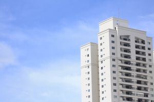 apartment building residential building blue sky building soft clouds white