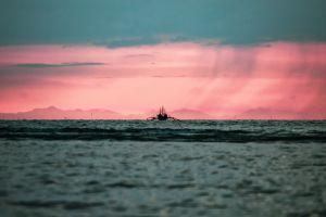 boat ocean pink sky beach