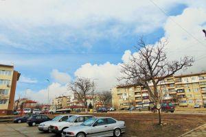 buildings sky trees street building vehicle tree clouds town road