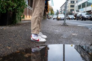 cars standing legs sneakers street person white shoes nike pavement reflection
