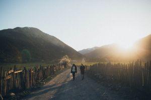 roadway sunlight scenery wooden fence sky environment peaceful dirt road idyllic dawn