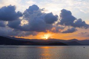 sunset scenic nature watercraft sea timelapse golden hour clouds water sunbeam