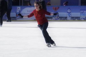 young woman skating on ice skating rink performing winter
