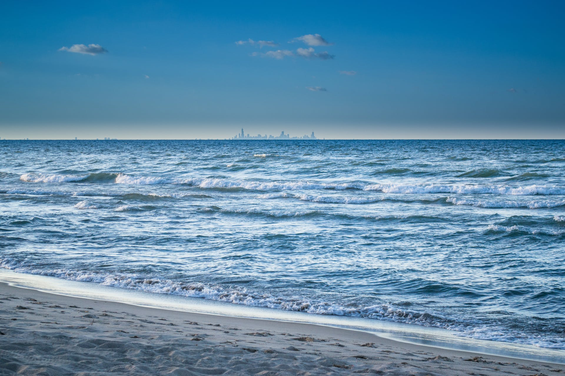 blue sky daytime shore coast wide angle photography ocean nature sand clouds water