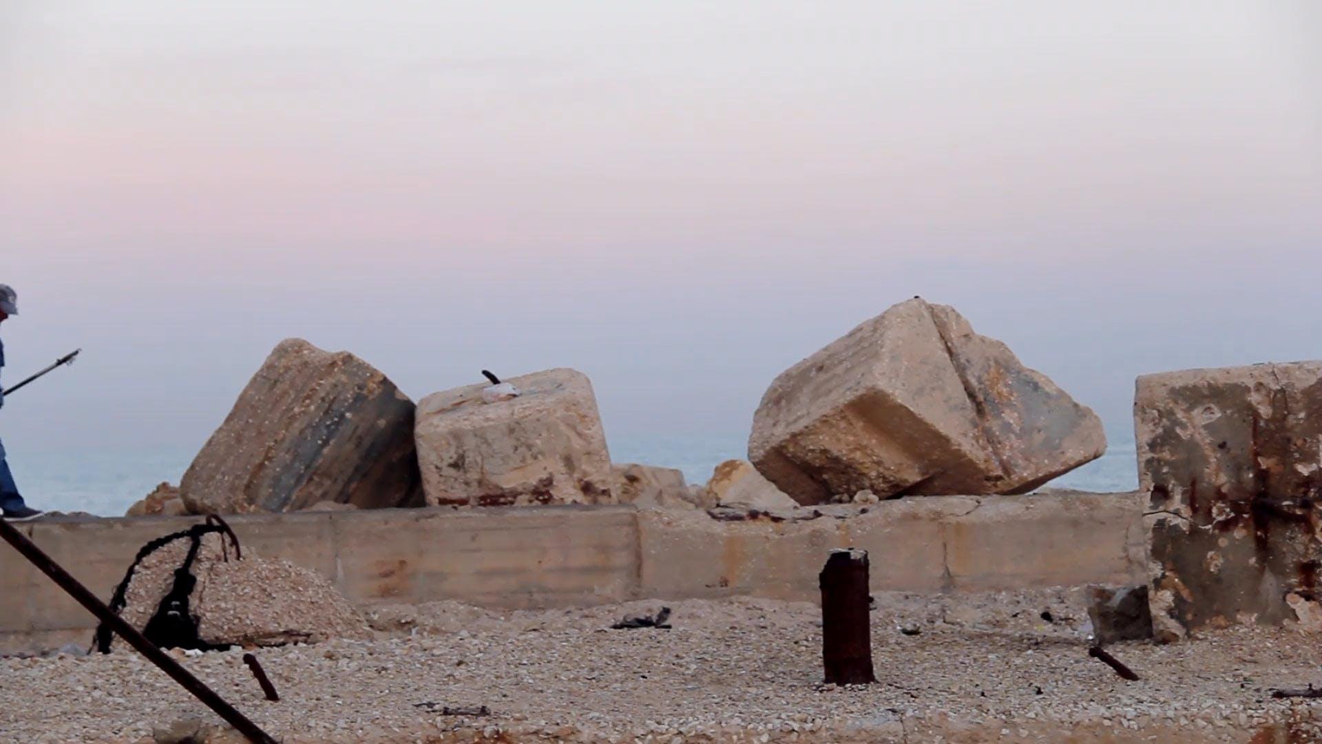 sand rocks person walking boulders man fishing rod fisherman bay