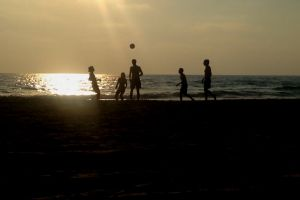 beach sunset seashore man sea kickball waves ball kids people