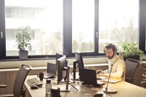 businessman headphone seat indoors technology work person sit desk occupation