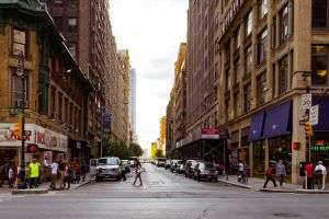 commerce pedestrian crossing clouds glass items buildings skyline urban pavement tourism cars