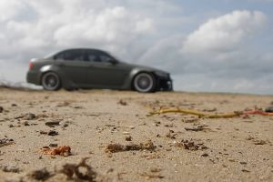 depth of field blurred driving person man car vehicle sand
