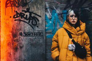 eyewear winter jacket street graffiti urban pose wear fashion wooden wall woman