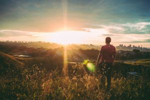 field light sky boy sunglare clouds landscape person evening sunset